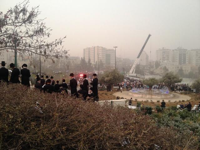 Judeus ultra-ortodoxos assistem a reza coletiva de cima de um morro. Crédito Diogo Bercito/Folhapress