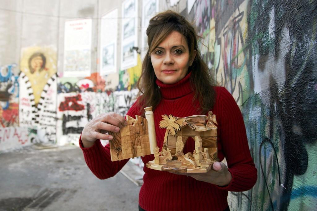 Claire Anastas segura artesanato que vende diante do muro, em Belém. Crédito Muhesen Amren/Folhapress