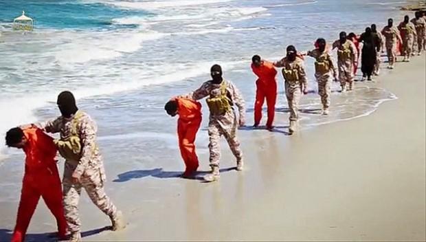 Membros do grupo Estado Islâmico aparecem com prisioneiros em alguma parte do sudeste da Líbia. Crédito Associated Press