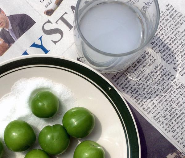 Ameixas verdes com sal e um copo de arak, bebida alcoólica de anis. Crédito Diogo Bercito/Folhapress
