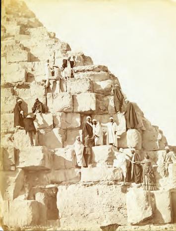 Dom Pedro 2º sobe a pirâmide de Quéops (à esquerda, sendo ajudado por egípcios). Crédito Acervo da Fundação Biblioteca Nacional do  Brasil
