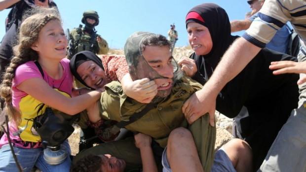Soldado é impedido de prender criança palestina. Crédito AFP