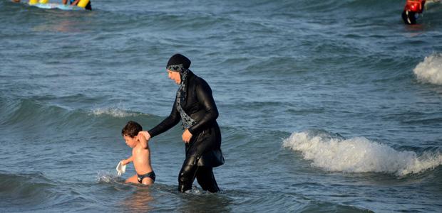 Mulher vai à praia nas proximidades de Tunis usando o burquíni, neste mês. Crédito Fethi Belaid/AFP